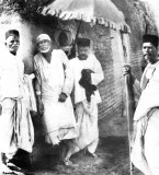 Orignal Picture of Shirdi Sai Baba, leaning against the wall of his masjid, with devotees