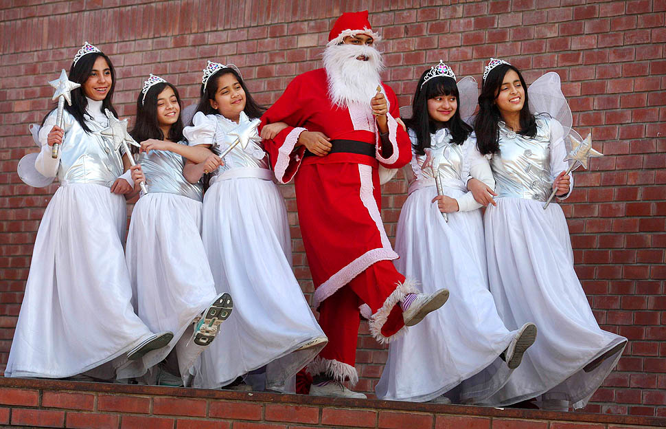 Student dressed up as santa claus dances with other students during